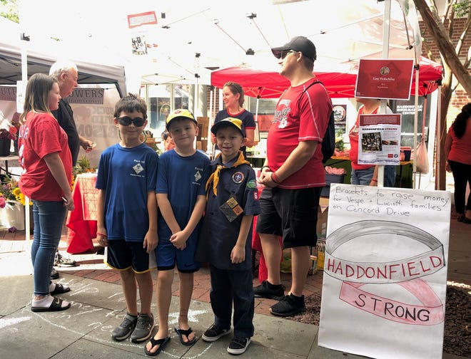 Matt Meaney (from left), Ryan Blackburn and Troy Bittner of Haddonfield Cub Scout Pack 65 show their support for neighbors during a 'Haddonfield Strong' drive at the Haddonfield Farmers Market on Aug. 10. The campaign to raise money for local flood victims includes the sale of wristbands for a $3 donation.