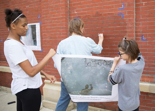 "Jyle Harris, left, and Lillian Kirk, right, hold up a photo advertising the up and coming ""Through our Eyes"" photo exhibit at the Carlisle Building in Downtown Chillicothe."