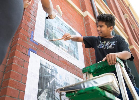 Malachai Robinson helps paste up signs advertising for an exhibiting spotlighting photos taken by local youth through the Ross County Community Action and Athens Photo Project outside the Carlisle building in downtown Chillicothe on August 14, 2019.