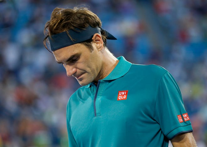 Roger Federer packs up as rain begins to fall in the second set during the Western & Southern Open match between Roger Federer and Juan Ignacio Londero at the Lindner Family Tennis Center in Mason, Ohio, on Tuesday, Aug. 13, 2019. Federer won in straight sets, 6-3, 6-4.