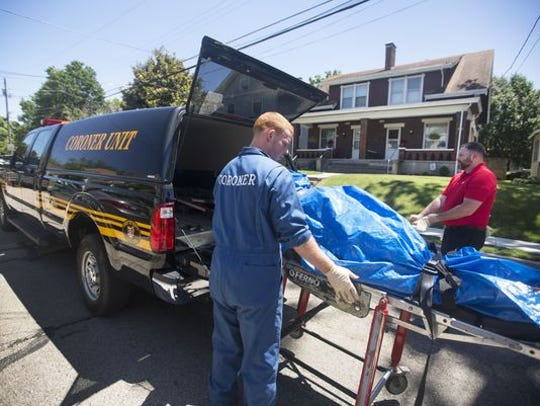 Coroner's investigators remove the body of a man who died from opioid overdose in Cincinnati.
