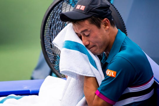 Kei Nishikori of Japan rests between sets against Yoshihito Nishioka of Japan on the Grandstand Court at the Western & Southern Open Wednesday, August 14, 2019 in Mason, Ohio.