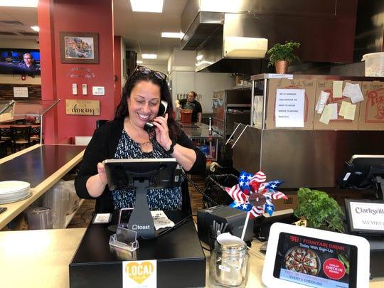 Executive Chef of Caprigios Pizza, Ilona Rivera takes a phone order