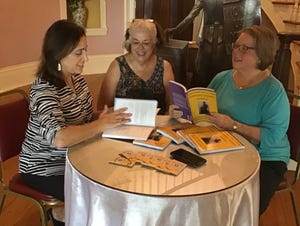 Tennessee Triumph steering committee members, from the left, Michele Newell, Martha Pile and Brenda Harper discuss sales strategies for the suffrage cookbook as part of fundraising efforts for the suffrage statue.