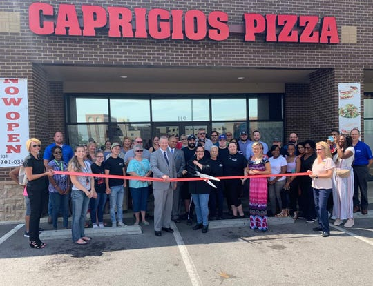 Ilona Rivera cuts a ribbon during the grand opening of Caprigios Pizza, Aug. 12, 2019.