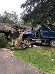 Three people escaped injury early Wednesday morning when a dump truck crashed into the front of a home in South Brunswick Police Department.