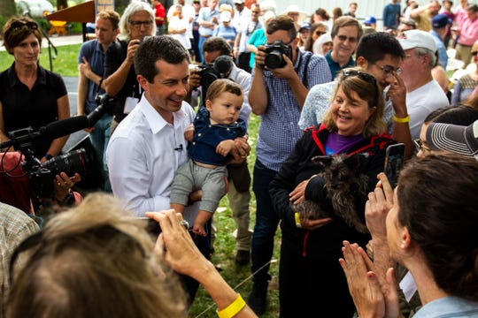 Democratic presidential candidate Pete Buttigieg, mayor of South Bend, Indiana, holds a baby while taking photos at the rope line, Wednesday, Aug. 14, 2019, at the Cedar County Fairgrounds in Tipton, Iowa.