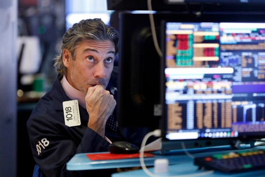 Trader John Romolo works on the floor of the New York Stock Exchange, Wednesday, Aug. 14, 2019. Stocks are falling sharply after the bond market threw up another warning flag on the economy. (AP Photo/Richard Drew)