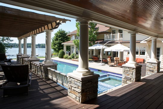 Standing on the porch of the guest house in this three-sided compound, you look left down the shaded colonnade, then right over to the main house and out to the pool and lake.This two-story guest house also serves as the pool house with one wall of refrigerators and freezers for refreshments.