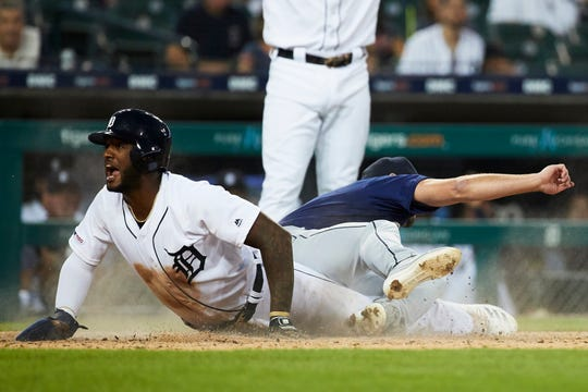 Detroit Tigers left fielder Niko Goodrum scores on a wild pitch ahead of the tag by Seattle Mariners starting pitcher Zac Grotz in the fourth inning at Comerica Park, Aug. 13, 2019.