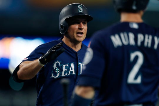 Kyle Seager is greeted at the dugout by Mariners teammate Tom Murphy after a three-run home run during the sixth inning.