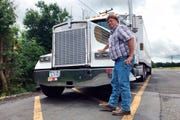 In this June 13, 2019 photo, truck driver Terry Button poses with his truck during at stop in Opal, Va., Thursday, June 13, 2019. The Trump administration has moved a step closer to relaxing federal regulations governing the amount of time truck drivers can spend behind the wheel.