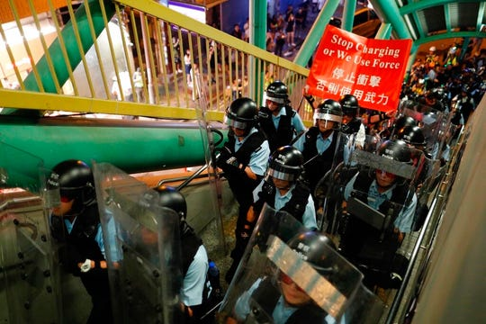 Police move out from the Shum Shui Po police station to confront protesters in Hong Kong on Wednesday, Aug. 14, 2019.  German Chancellor Angela Merkel is calling for a peaceful solution to the unrest in Hong Kong amid fears China could use force to quell pro-democracy protests.