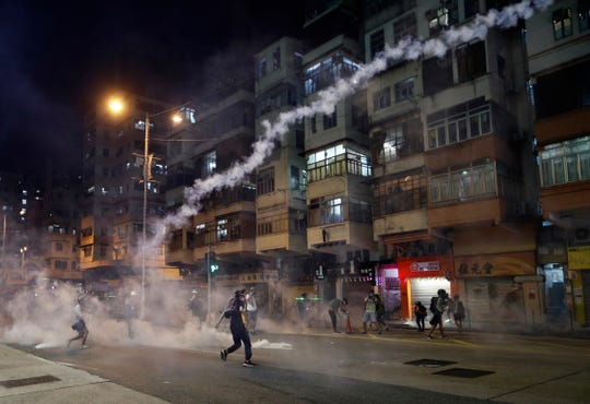 Protesters react to tear gas from Shum Shui Po police station in Hong Kong on Wednesday, Aug. 14, 2019. German Chancellor Angela Merkel is calling for a peaceful solution to the unrest in Hong Kong amid fears China could use force to quell pro-democracy protests.