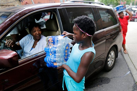 Elaine Younger, 11, and Tahvion Williams, 14, right, load water in their family's van at the Newark Health Department in Newark, N.J., Wednesday, Aug. 14, 2019. Residents began picking up bottled water on Monday, days after elevated lead levels were found in homes where city-issued filters had been distributed months ago as part of an ongoing effort to combat contamination.