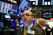 In this Tuesday, Aug. 13, 2019, file photo trader Andrew Silverman works on the floor of the New York Stock Exchange. The threat of a recession doesn't seem so remote anymore, and stocks sank Wednesday after the bond market threw up one of its last remaining warning flags on the economy's health.