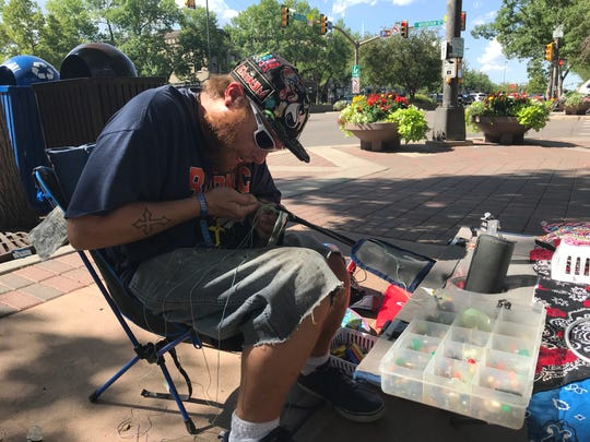 Nick Strange makes and sells jewelry at the corner of College and Mountain avenues. Strange, who is homeless, said following city rules against blocking sidewalks and business entryways is not difficult.