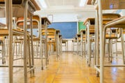 A stock photo of desks in a classroom.