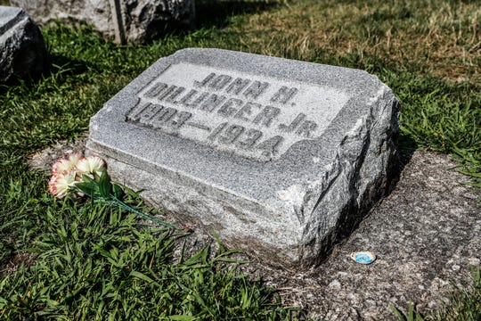 The grave of John Dillinger Jr. sits inside the walls of Crown Hill Cemetery in Indianapolis. Dillinger's smaller headstone sits in the family plot marked by a larger headstone. Small chunks of the stone, which may have been replaced once, have been chipped off by visitors over the years.