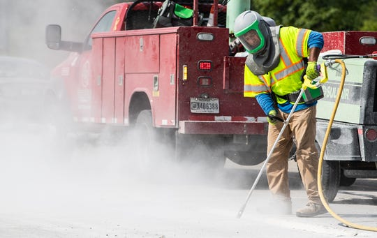 A worker uses forced air to remove debris from a hole set to be filled with concrete along a closed section of I-465 on Wednesday, Aug. 14, 2019.