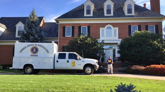 The FBI, Treasury and other law enforcement officers conduct an investigation at the Carmel home of American Senior Communities CEO James Burkhart on Sept. 15, 2015.