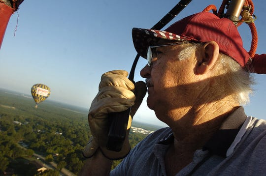 Pat Harwell talks on a radio to a nearby hot air Balloon while floating through the skies of Shreveport/Bossier before the annual Red River Balloon Fest and Sky Parade.--Douglas Collier/the Times
