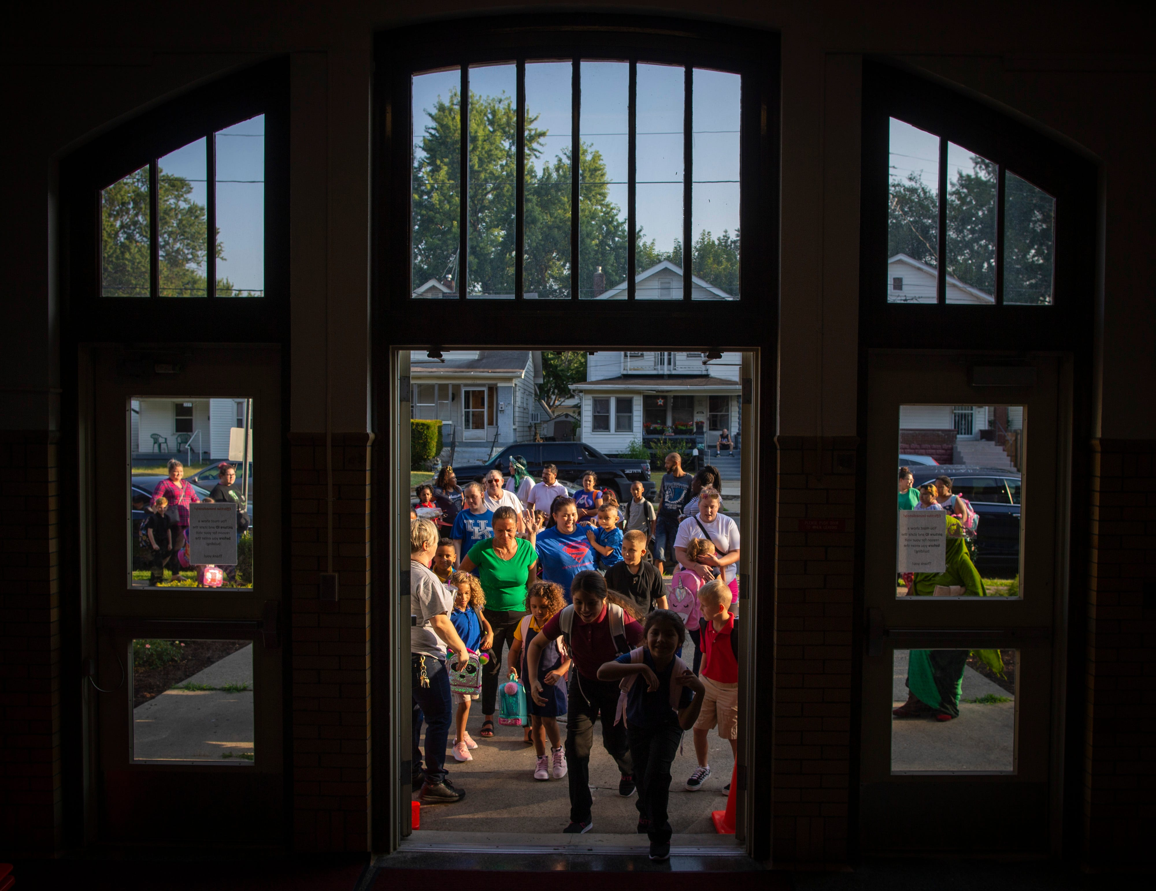 Students make their way inside Semple Elementary School, located near Churchill Downs, on the first day of school. Aug. 14, 2019