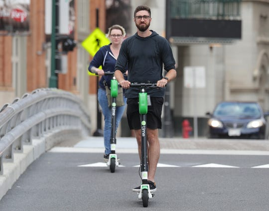 A man and woman ride Lime electric scooters across the Wells Street bridge in Milwaukee in August.