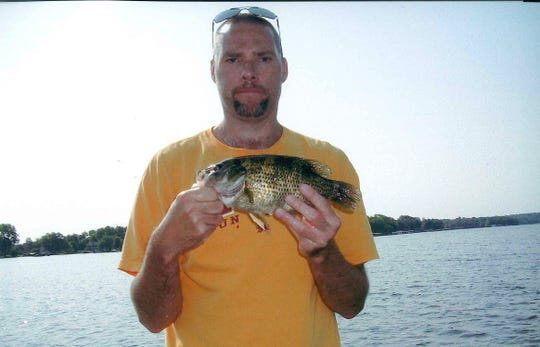 Jeffrey Henderson of Milwaukee holds an 11-inch rock bass he caught on Lake Nagawicka in southeastern Wisconsin. The fish is the state record in the Live Release program.