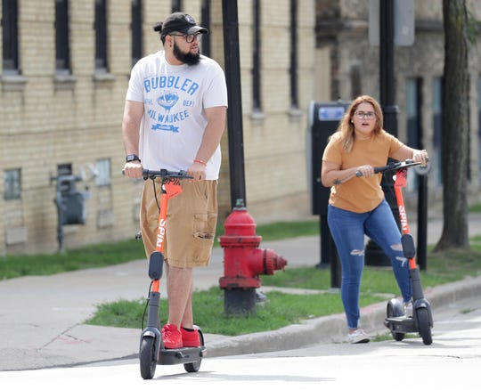 Zech Simmons, right, looks for traffic and Paola Rodriguez, both from Milwaukee, ride Spin electric scooters in Milwaukee on Wednesday, Aug. 14, 2019.