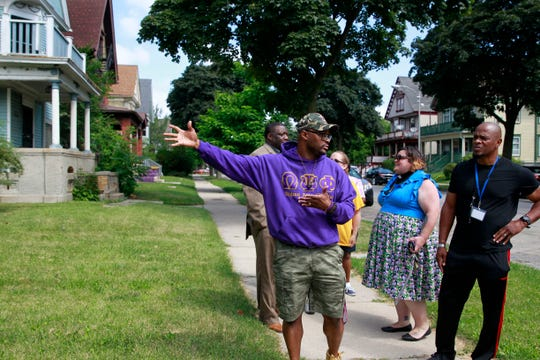 Ramel Kweku Akyirefi Smith, co-organizer of the Day of Love community event, with Marcel Clarke, left rear, Anna Lamer, Pastor Lindsey Beukelman and Horace Craft, right, he points to a lot where backpacks will be given out at the event Aug. 24.