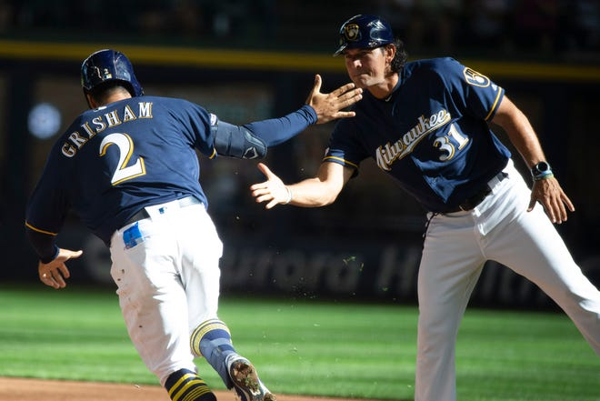 The Brewers' Trent Grisham celebrates with first base coach Carlos Subero after hitting a three-run home run in the bottom of the eighth inning Wednesday at Miller Park.