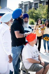 Mayor Dan Bukiewicz, bottom right, gets a turban tied on his head by members of the Sikh community at the CAFE event in Drexel Town Square on Aug. 3.