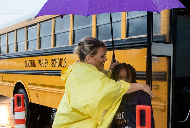 Boley Elementary School principal Sandy Bates hugs a student after being dropped off by the bus on the first day of school at the temporary location of the school in West Monroe, La. on Aug. 14. The original location of the school burned in a fire on April 13.