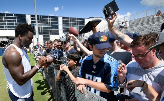 Tennessee Titans wide receiver Corey Davis (84) signs autographs for fans after a joint training camp practice against the New England Patriots at Saint Thomas Sports Park on Aug. 14, 2019. The free Titans training camp open practices are unlikely to happen this year.
