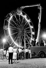 The Metro Fire Department's 70-foot snorkel rescuer hovers at the top of the Fair Park Ferris wheel during a rescue operation that lasted several hours late May 4, 1963. Thirty-five people were taken from the wheel in the harrowing operation after a snapped cable on the Ferris wheel stranded them high above the ground. All were taken from the 55-foot wheel without injury.
