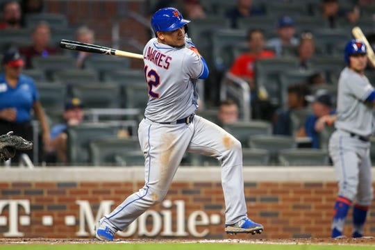 Aug 13, 2019; Atlanta, GA, USA; New York Mets center fielder Juan Lagares (12) hits a RBI single against the Atlanta Braves in the eighth inning at SunTrust Park. Mandatory Credit: Brett Davis-USA TODAY Sports