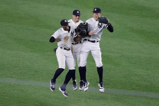 New York Yankees' Cameron Maybin, Mike Tauchman and Aaron Judge, from left, celebrate after the team's baseball game against the Baltimore Orioles on Tuesday, Aug. 13, 2019, in New York. The Yankees won 8-3.