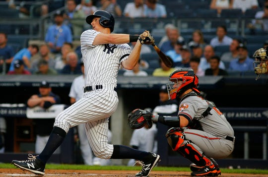 Aug 13, 2019; Bronx, NY, USA; New York Yankees first baseman DJ LeMahieu (26) hits a solo home run against the Baltimore Orioles during the first inning at Yankee Stadium.