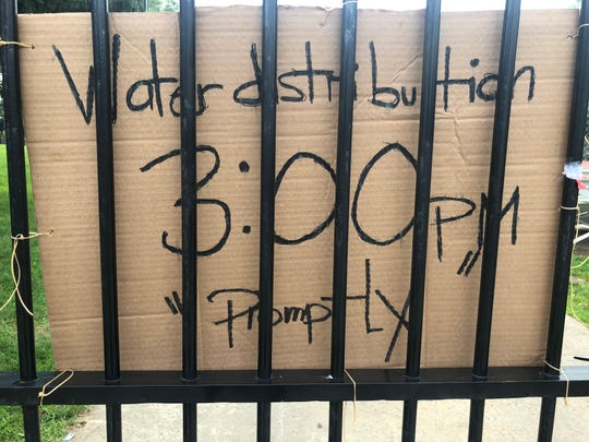 Signs greeting Newark residents seeking free water bottles at a south Ward distribution site Tuesday
