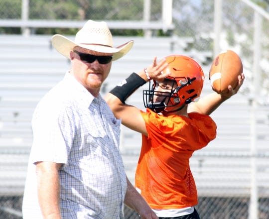Lordsburg Mavericks Coach Dale Hooper oversees practice while sophomore quarterback Maverick Contreras works with receivers.