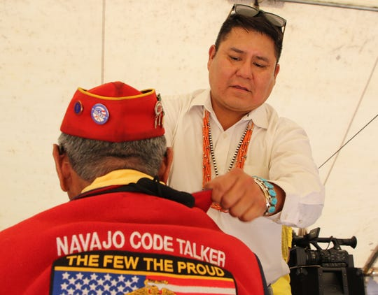 Navajo Nation Council Delegate Nathaniel Brown places a bolo tie on Navajo Code Talker Peter MacDonald Sr.  during the Navajo Code Talkers Day honoring ceremony on Aug. 14 in Window Rock, Arizona.
