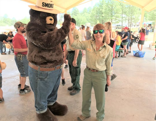 Jodie Canfield and Smokey Bear high five for fire prevention.