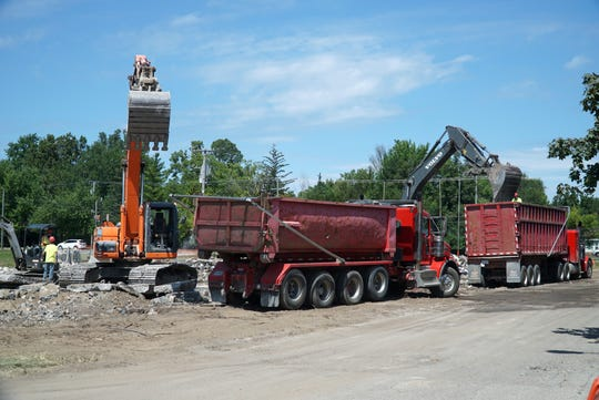 Dump trucks line up at the old court building in Farmington off Ten Mile Road on Aug. 14 as the structure is leveled and carted away.