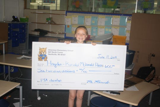 Hayden Rosenau holds up a larger-than-life check that was presented to her by the Amerman Elementary School PTA. The amount of the check matched the amount of money Rosenau raised for Detroit's Ronald McDonald House.