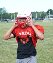 Canton quarterback Ben Stesiak straps on his helmet before an Aug. 14 practice.