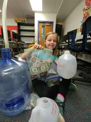 Hayden Rosenau holds up a portion of the money she raised for Detroit's Ronald McDonald House.