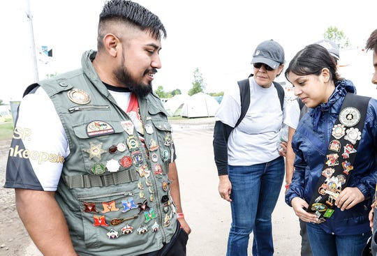 Francisco Vasquez of New York and Flower Moreno of Texas look at each other's location pins they gathered Wednesday, Aug. 14, 2019, at the Pathfinders convention on the EAA grounds in Oshkosh, Wis. About 55,000 people were on hand to take part in the event which happens every five years on the EAA grounds.