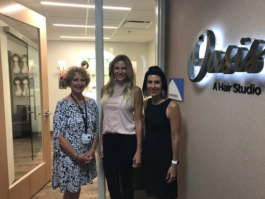 From Left to Right: Liz Janzen, Rebecca Hurst and Sandy Andreini pose in front of the Oasis, a salon for people dealing with hair loss.