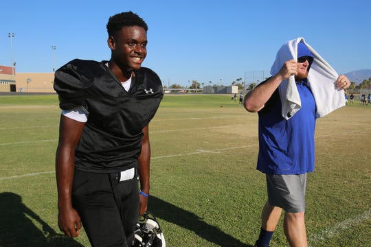 Cathedral City High School quarterback Oshea Wallace, left, and assistant coach R.K. Carrick share a laugh during practice at Cathedral City High School in Cathedral City, Calif., on Tuesday, August 13, 2019.